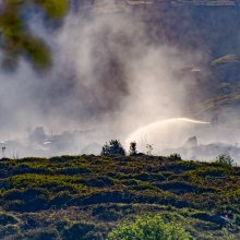 Firefighters direct their hoses over smouldering moorside near Ilkley