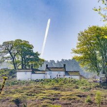 A jet line high in the sky over White Wells bath house on Ilkley Moor
